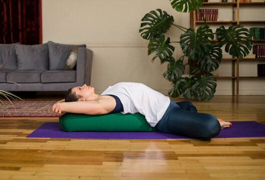 yoga woman in sportswear relaxes on bolster mat in the room