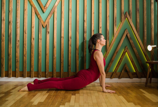 female yoga teacher in a burgundy sports jumpsuit performs exercises for a healthy back in the gym