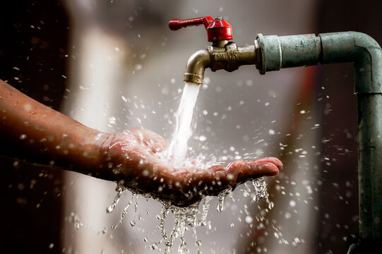 Clean water flows freshly from the tap into the palm of your hand. Focus on the faucet.