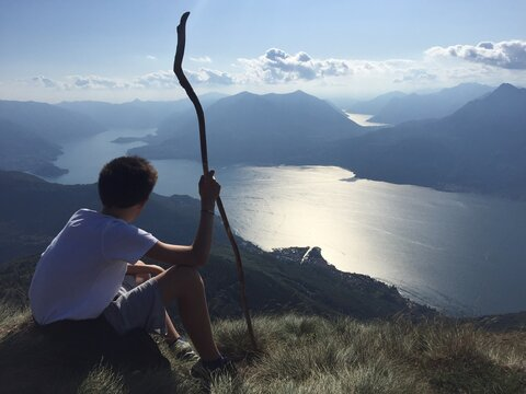 Rear View Of Boy Holding Stick While Sitting On Mountain