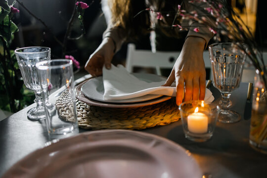 female hands serve a napkin on a table with flowers