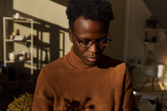 People, ethnicity and race concept. Portrait of fashionable young Afro American man with short curly hair posing indoors in stylish sunlit room, looking down with thoughtful facial expression