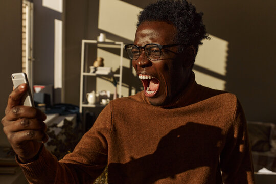 Portrait of stressed enraged young dark skinned businessman in eyewear holding smart phone in front of his face, opening mouth widely, screaming, being furious because of bad internet connection
