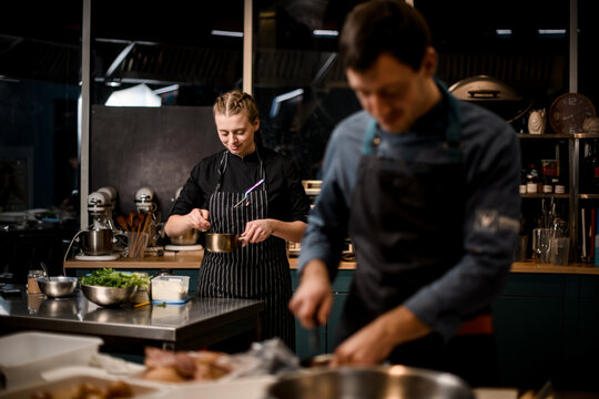 view on young attractive woman chefs in restaurant kitchen preparing dish.