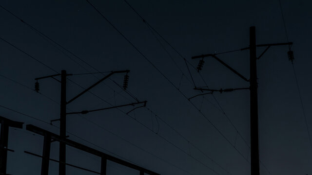 Power lines over the railroad at night. Silhouette of power lines against the sky.