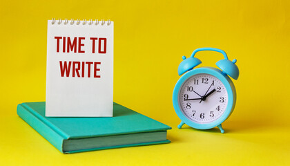 Text for writing words Time to write, text is written on notepad and yellow background. Nearby alarm clock and green notepad. Business concept for urgent traffic.