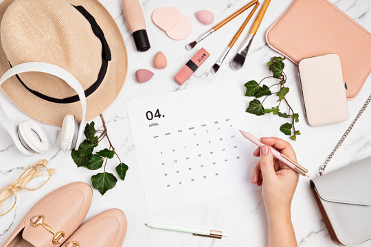 Flat lay with calendar for april with woman fashion spring accessories. Social media blog, schedule, planning concept. Flatlay, top view