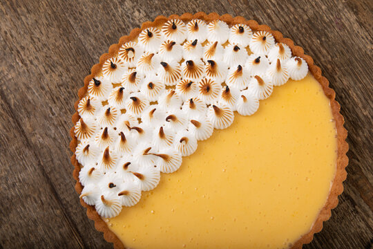 Traditional sweet pastry lemon tart with burnt meringue on wooden table