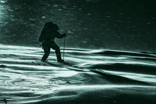 Climber fights with bad weather in the winter mountains, horror