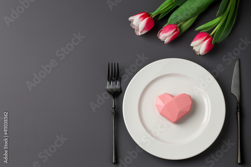 Creative table setting with hearts on a white plate, black fork and knife, tulips on a dark background. Valentine's Day, Wedding Day, Birthday, Women's Day and Mother's Day. Flat lay. Copy space