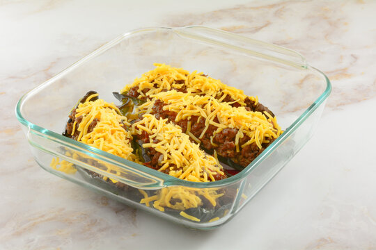 Preparing stuffed poblano peppers in glass baking dish by adding shredded cheese on top