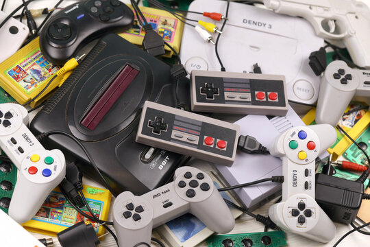 KHARKOV, UKRAINE - DECEMBER 27, 2020: Pile of old 8-bit video game consoles and many gaming accessories like joysticks and cartridges. Old school retro gaming
