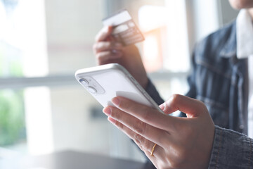 Mobile banking, Online shopping, digital banking, internet payment concept. Woman hand using mobile smart phone payments and credit card for online shopping - fototapety na wymiar