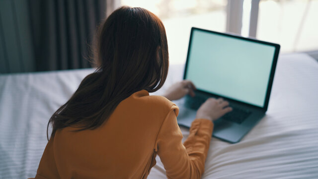 woman in bedroom lies on bed in front of laptop communication technology