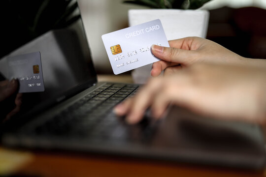 The person holds a silver credit card and is filling out their credit card information to pay for goods online, credit cards can pay for goods and services both in the storefront and online shopping.