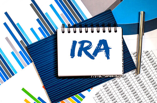 Notepad with IRA on a table with charts