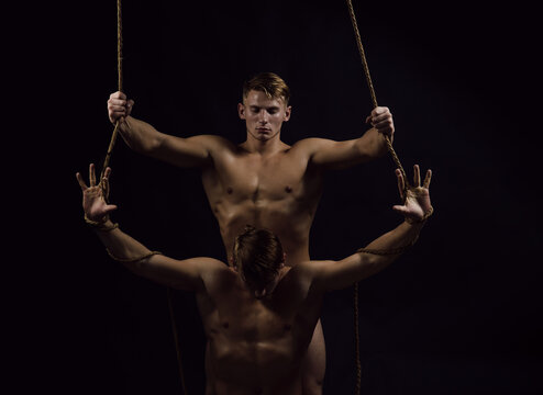 Man rope. Young twins athletic sexual guys with powerful shoulders, abdomen and chest, abs or six pack. Male hunk with naked body, bare torso.