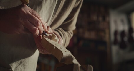 Cinematic shot of experienced master artisan luthier painstaking detail work on fine quality wood...