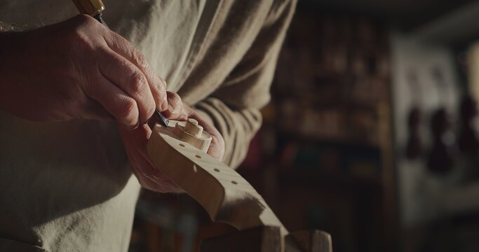 Cinematic shot of experienced master artisan luthier painstaking detail work on fine quality wood violin in creative workshop.Concept of spiritual instrument,handmade, art, orchestra, artisan,passion