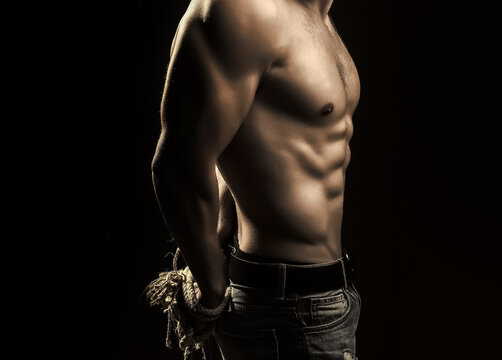 Sexy man with muscular body with tied hands by rope.