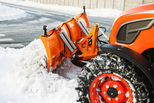The tractor cleans the sidewalk in the winter in January