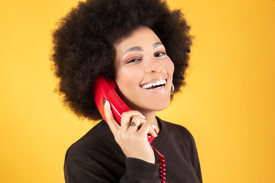 Mixed afro woman, talking on retro red phone, happy smiling, yellow background