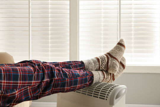 Man warming feet on electric heater at home, closeup