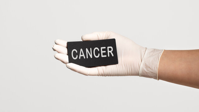 Closeup of the hand in a white sterile glove holding a card with word - CANCER