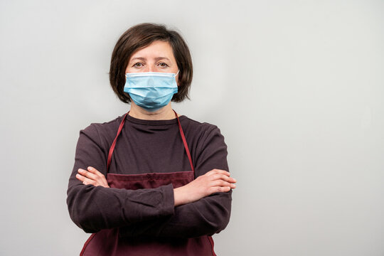 Portrait of woman wearing an apron and a protective mask with her arms crossed. During confinement, Worker with allergies.