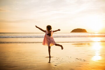 Full Length Rear View Of Girl Dancing While Looking At Sea During Sunset