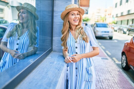 Young beautiful blonde woman on vacation wearing summer hat smiling happy. Leaning on the wall with smile on face at street of city.