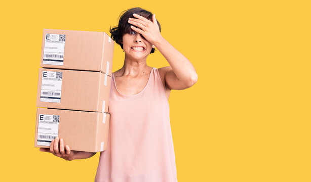 Beautiful young woman with short hair holding delivery packages stressed and frustrated with hand on head, surprised and angry face