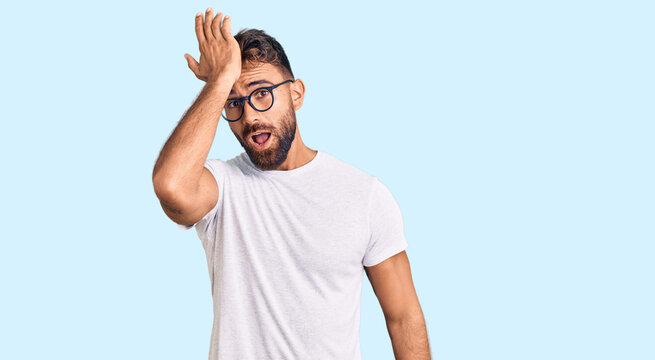 Young hispanic man wearing casual clothes and glasses surprised with hand on head for mistake, remember error. forgot, bad memory concept.