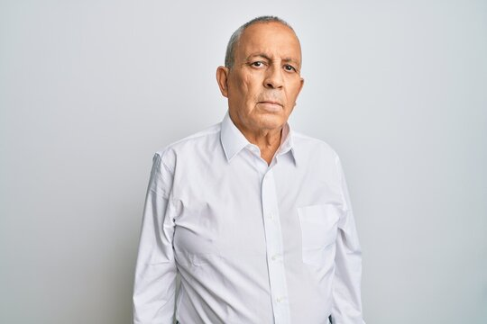 Handsome senior man wearing casual white shirt relaxed with serious expression on face. simple and natural looking at the camera.