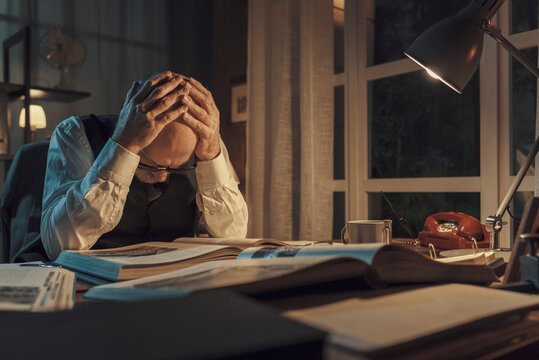 Exhausted professor sitting at desk and studying