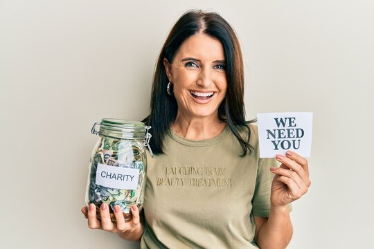 Middle age brunette woman holding charity jar with money and we need you paper smiling and laughing hard out loud because funny crazy joke.