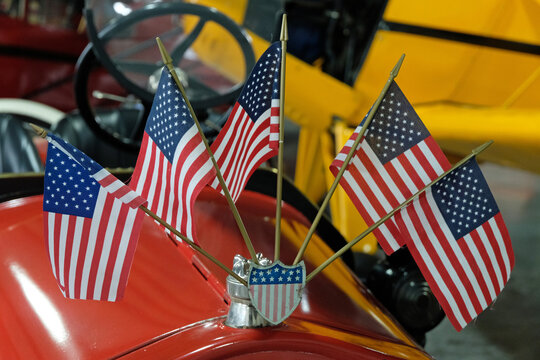 American flags on the front of a classic car