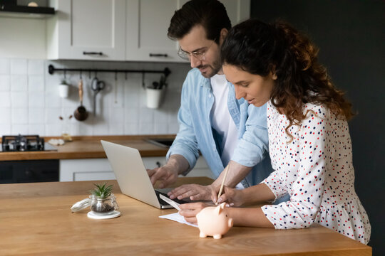 Concentrated millennial spouses calculating family budget paying utility bills online using laptop. Busy married couple check review loan payments planning expenses choose effective way to save money