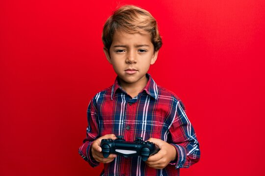 Adorable latin kid playing video game holding controller depressed and worry for distress, crying angry and afraid. sad expression.