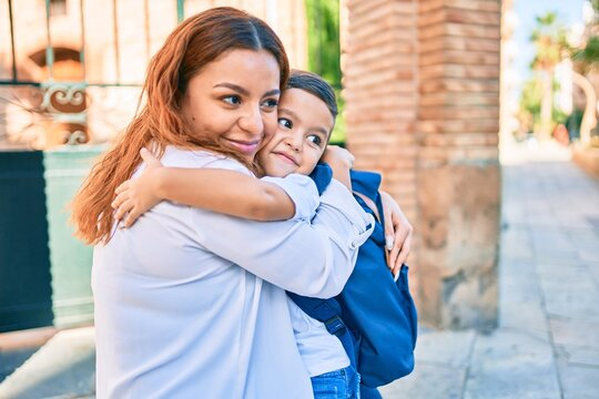 Adorable latin student boy and mom hugging at the city.