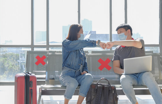 Two asian young traveller wearing medical face mask, fist bump greeting each other with new normal way and keep social distancing to prevention coronavirus outbreak. COVID-19 awareness concept.