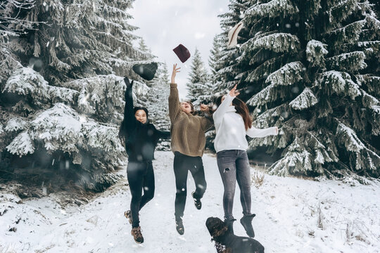 A group of three friends cheerfully jump and throw up their hats against the snow-covered winter landscape.Winter lifestyle.enjoy the little things