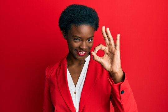 Young african american girl wearing business clothes smiling positive doing ok sign with hand and fingers. successful expression.