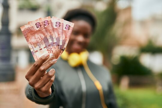 Young african american girl using headphones holding south africa rands at the city.