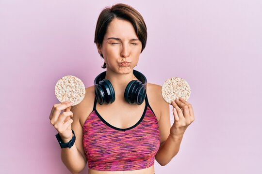 Young brunette woman with short hair wearing sportswear holding rice cakes puffing cheeks with funny face. mouth inflated with air, catching air.