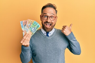 Handsome middle age man holding australian dollars pointing thumb up to the side smiling happy with...
