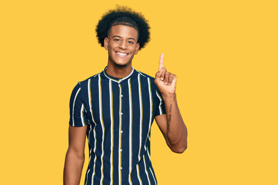African american man with afro hair wearing casual clothes showing and pointing up with finger number one while smiling confident and happy.