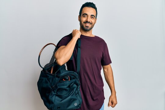 Young hispanic man holding gym bag looking positive and happy standing and smiling with a confident smile showing teeth