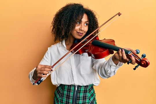 Beautiful african american woman with afro hair playing classical violin smiling looking to the side and staring away thinking.