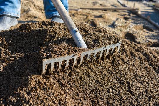 The gardener loosens the ground with a rake
